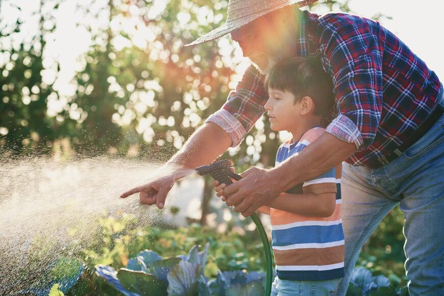 abuelo enseñando a regar al nieto_consumo sostenible del agua